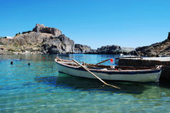 Boat in bay. Wooden boat in peaceful blue bay, Rhodes island, Greece Royalty Free Stock Images