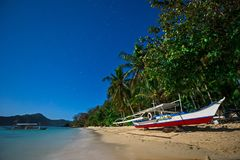 Boat on the beach in the moonlight. Moonscape in the Philippines with traditional banca boat on a beach, with starry sky above Stock Photos