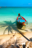 Boat at the beach with Palm Shades. Boat on the beach with palm trees and shade from trees Stock Photo