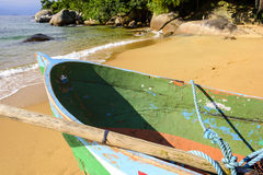 Boat on the beach. Rowing fishing boat in wood on the sand of the Red Beach on the Big Island in Angra dos Reis Royalty Free Stock Photos