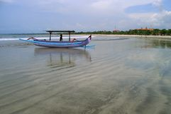 Boat, Beach & Sea. Seascape with a boat and the boy on a beach of island Bali Royalty Free Stock Image