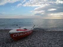 Boat on the beach. Summer evening at the Black Sea, the beautiful clouds at sunset Stock Photos