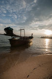 Boat on the beach at sunrise in tide time. Stock Photo