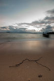 Boat on the beach at sunrise in tide time. Stock Image
