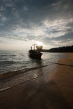 Boat on the beach at sunrise in tide time. Royalty Free Stock Photos