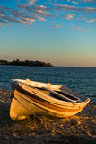 Boat on a beach at sunset with ruins of old roman fortress in backround, Sithonia Stock Images
