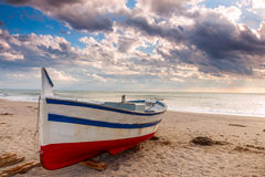 Boat on the beach at sunset time Royalty Free Stock Image