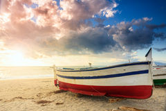 Boat on the beach at sunset time Royalty Free Stock Photos