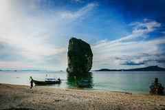 Boat on the beach of Thailand. Near with a huge rock. Picturesque clear blue sky Royalty Free Stock Photography
