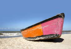 Boat on the beach under a clear blue sky. A boat sits on the beach under a clear blue sky with crashing surf Stock Images