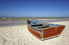 Boat on the beach under a clear blue sky. A boat sits on the beach under a clear blue sky with crashing surf Stock Photography