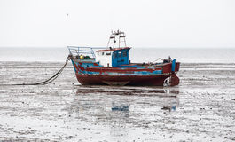 Boat beached on sands at low tide. Motor boat beached on the sands at Southend on the Thames estuary royalty free stock photography