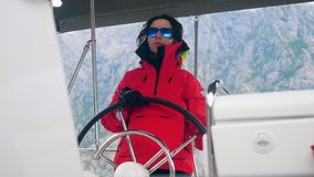 A boat is being driven by a woman in a parka. 4K stock video footage