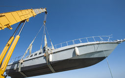 Boat being lifted by heavy crane machinery Stock Photography