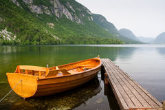 Boat berth by the tranquil lake pier with mountain. As background stock image