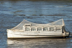 Boat with bird netting stranded in mud royalty free stock images