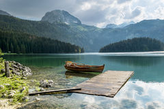 Boat on Black Lake in the national park Durmitor and mountains i Royalty Free Stock Photo