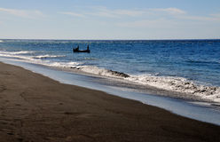 Boat by a black sand beach Royalty Free Stock Images