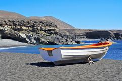 Boat in a black sand beach in Fuerteventura, Spain Royalty Free Stock Image