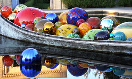 Glass spheres in a boat. Floating in a pool Royalty Free Stock Photography