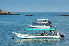 Boat on blue lagoon Stock Photos