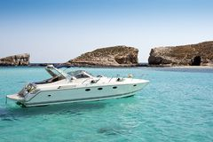 Boat on blue lagoon. Speedboat and blue lagoon water in mediterranean sea Royalty Free Stock Images