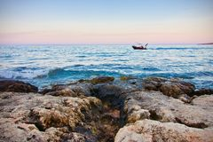 Boat on blue ocean at a cliff, Mallorca, Spain Stock Photography