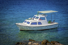 Boat on blue sea. Moment caught in lens..sea and boat in the background, in the game of colors, green sea and beautiful reflections of the sun in the sea Royalty Free Stock Photo