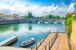Boat in blue water near pier and stone arch Tiberius bridge Ponte di Tiberio, Augustus Bridge over Marecchia river in Rimini. Boat in blue water near pier and stock image