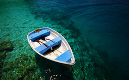 Boat in blue water. Small white boat on the tranquil turquoise water in tropics Royalty Free Stock Image