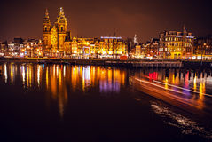 Boat with blur light moving on night canals of Amsterdam. Royalty Free Stock Photos
