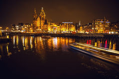 Boat with blur light moving on night canals of Amsterdam. Royalty Free Stock Photo