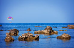 Boat with blurred paraglide behind the rocks Royalty Free Stock Photo