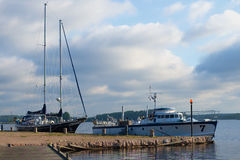 A boat and a boat at the pier on the Saimaa lake, august morning. Lappeenranta, Finland Stock Photo