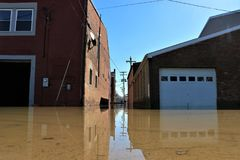 Boat boating down flooded road in Aurora, Indiana. February 2018 flooding of Aurora, Indiana from the Ohio River. Garages under water Royalty Free Stock Photography