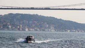 Boat on the Bosphorus under a bridge Stock Image