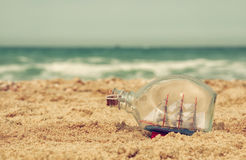Boat in the bottle on sea sand and ocean horizon Royalty Free Stock Photos