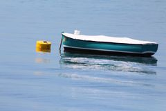 Boat and Bouy on the Water. The boat and the bouy are on the blue water sitting calmly. The bouy is holding the boat anchored to the bouy to make sure it doesn`t royalty free stock image
