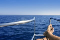 Boat bow with male man feet relaxed. Boat bow summer vacation with male man feet relaxed over blue ocean sea Royalty Free Stock Photos
