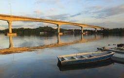 Boat and a bridge at sunrise Stock Photo