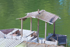Boat bridge with wooden boat and thatched roof. Royalty Free Stock Photography