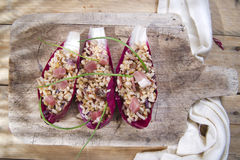 Boat of brown rice with red radicchio and speck Stock Photo
