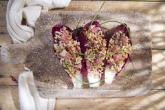 Boat of brown rice with red radicchio and speck. Presentation of brown rice with bacon and red radicchio Royalty Free Stock Image