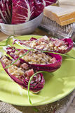 Boat of brown rice with red radicchio and speck. Presentation of brown rice with bacon and red radicchio Stock Photos