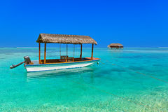 Boat and bungalow on Maldives island Stock Photo