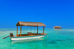 Boat and bungalow on Maldives island Stock Image