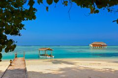 Boat and bungalow on Maldives island Stock Photos
