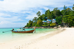 Boat and bungalows on the beach, Thailand. Traditional wooden boat and bungalows on the beach of Koh Lipe Island, Thailand Royalty Free Stock Images