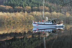Boat on the Caledonian Canal. A boat moored on the Caledonian Canal on a calm frosty morning with a strong reflection in the water stock image