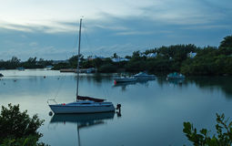 Boat in a Calm Harbour at Dawn. A singe boat, with others in the background, in a calm, natural harbour at dawn Stock Photos